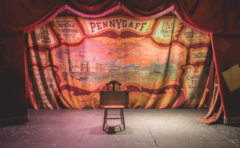theatre stage featuring a circus backdrop and large red velvet curtains around a single chair on stage